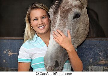 Blonde girl stroking horse