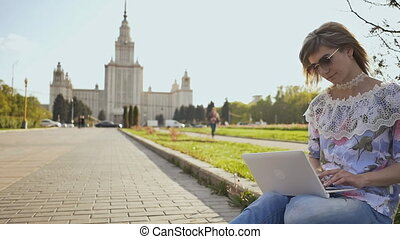 Blonde girl student working with a laptop on a square on the background of Lomonosov Moscow State University.