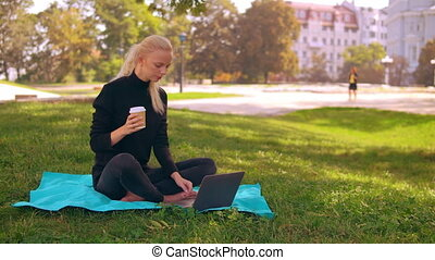 blonde girl use computer outdoors - young caucasian woman...