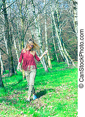 Blonde girl walking in the woods in the wild