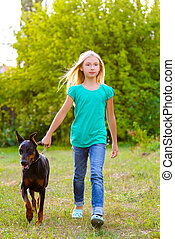 blonde girl walking with the dog or doberman in summer park