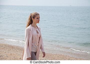 blonde girl walks along the beach of the sea coast
