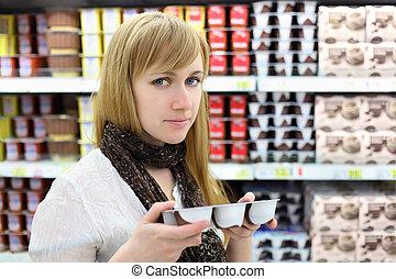 Blonde girl wearing scarf chooses yoghurt in store; shallow depth of field