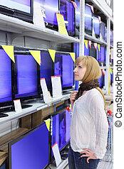 Blonde girl wearing scarf looks at plasma TVs in supermarket; shallow depth of field