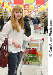 Blonde girl wearing white shirt and cart with food; shallow depth of field