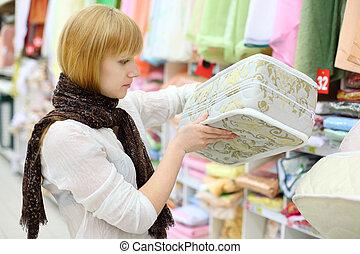 Blonde girl wearing white shirt chooses mattress in shop; shallow depth of field