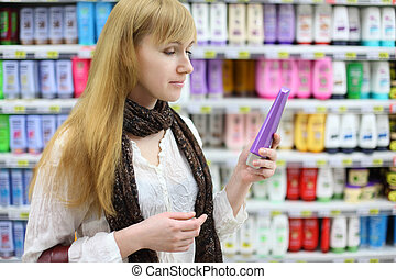 Blonde girl wearing white shirt chooses shampoo in large...
