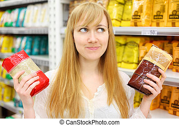 Blonde girl wearing white shirt chooses rice in store; shallow depth of field