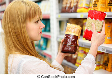 Blonde girl wearing white shirt compares rice in store; shallow depth of field