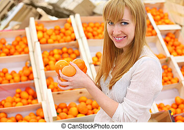 Blonde girl wearing white shirt holds oranges in store; shallow depth of field