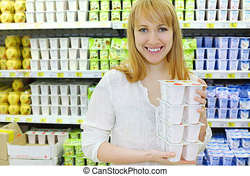 Blonde girl wearing white shirt keeps yoghurt in shop; shallow depth of field
