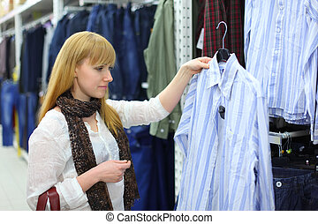 Blonde girl wearing white shirt looks at male shirt in shop; shallow depth of field