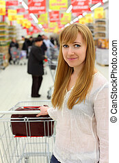 Blonde girl wearing white shirt with empty cart; shallow depth of field