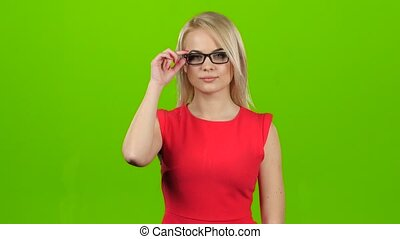 Blonde girl winks her eyes off glasses, green screen studio