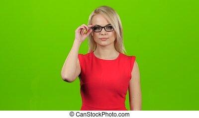 Blonde girl winks her eyes off glasses, green screen studio