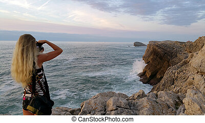 Blonde girl with a camera shooting sea from edge cliff