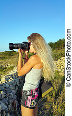 Blonde girl with a camera with a large lens shooting outdoor