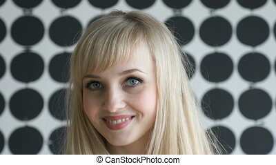 Blonde girl with a thick hair smiling for camera