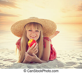 Blonde girl with apple on the beach.