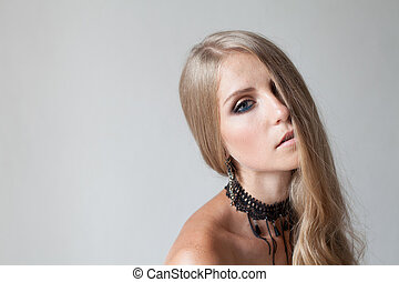 BLONDE GIRL WITH BLUE EYES MAKEUP ON WHITE BACKGROUND