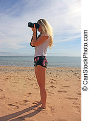 Blonde girl with camera shooting on the beach