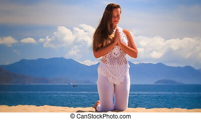 blonde girl with closed eyes in yoga asana touch hands...