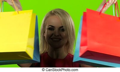 Blonde girl with colorful packages grimaces and smiles. Slow motion