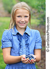 Blonde Girl with Fresh Picked Blueberries Smiling - Young...