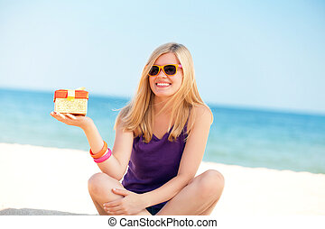 Blonde girl with gift at the beach.