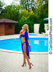 Blonde girl with long hair holding cocktail and posing near pool on the sun