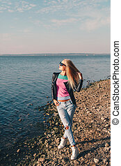 Blonde girl with long hair on a photo shoot by the sea - ...