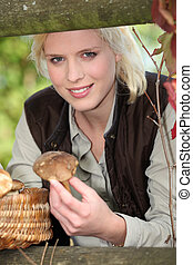 Blonde girl with mushrooms in hand