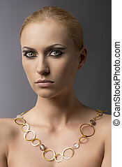 blonde girl with necklace in front of the camera