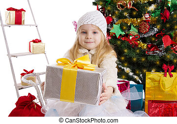 Blonde girl with present under Christmas tree