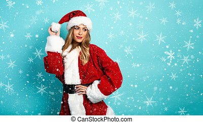 Blonde girl with Santa Claus costume on cyan background