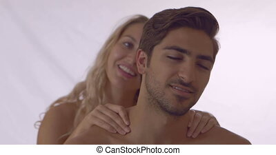Blonde giving her boyfriend a shoulder rub at home in...