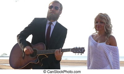 blonde guitarist plays for blonde woman on beach