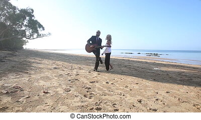 blonde guitarist plays on beach blonde girl flirts at dawn
