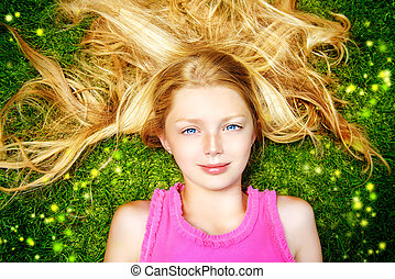 Beautiful smiling girl lying on a green lawn in the park. Sunny summer day.