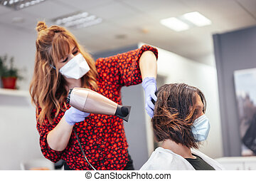 Blonde hairdresser with mask and gloves drying the client's ...