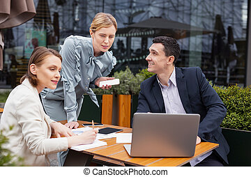 Blonde-haired businesswoman wearing stylish blouse joining staff meeting
