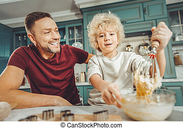Blonde-haired son holding bowl with baking mix for cookies
