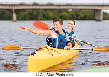 Blonde-haired trainer showing woman sitting in canoe correct direction
