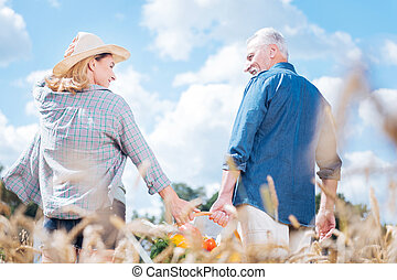 Blonde-haired wife looking at her handsome husband after gathering harvest