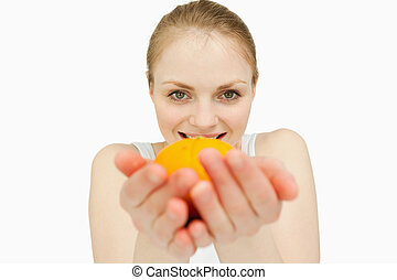 Blonde-haired woman holding a tangerine against white...