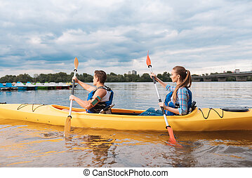 Blonde-haired woman kayaking with her man for the first time