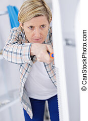 blonde handywoman cleaning fixing ventilation system