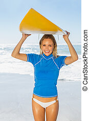 Blonde happy surfer holding her board on the beach on a sunny day
