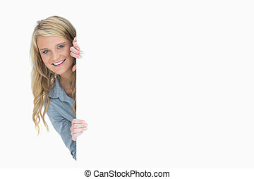 Blonde hiding behind a poster