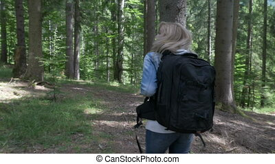 Blonde hiker woman with backpack walking on path of mountain...